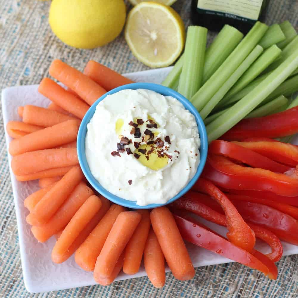 plate with lemon feta dip in a blue bowl with sliced veggies and lemons