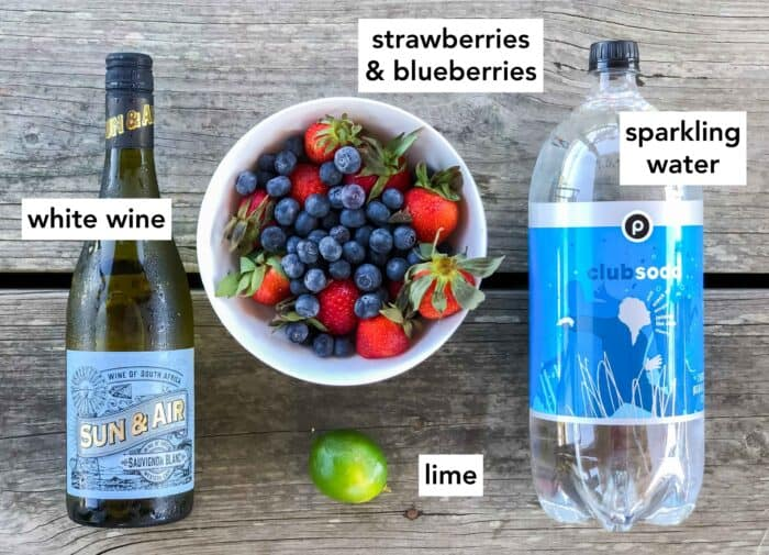 wooden table with white wine, bowl of strawberries and blueberries, one lime, and a bottle of club soda