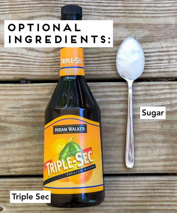 wooden table with bottle of triple sec and a spoon with sugar