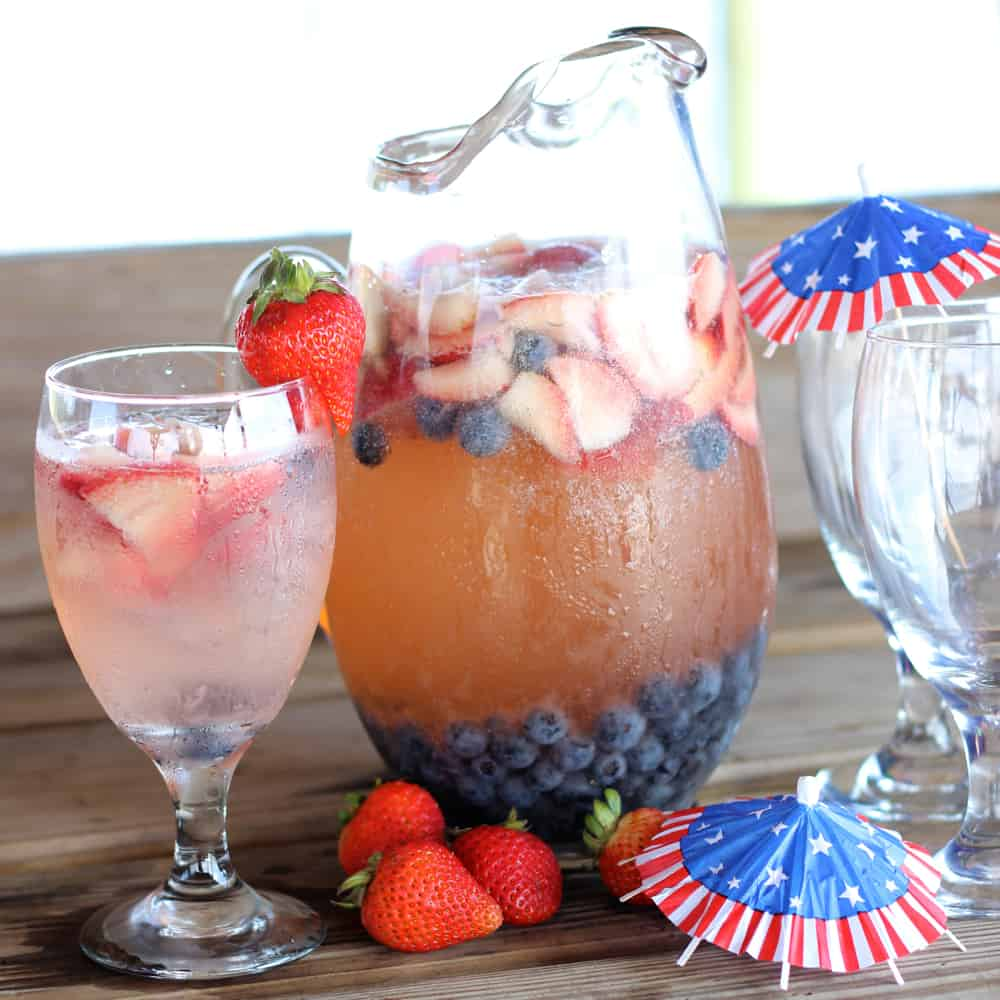 pitcher of sangria and a glass of red white and blue sangria with a strawberry on glass with 4th of July drink umbrellas