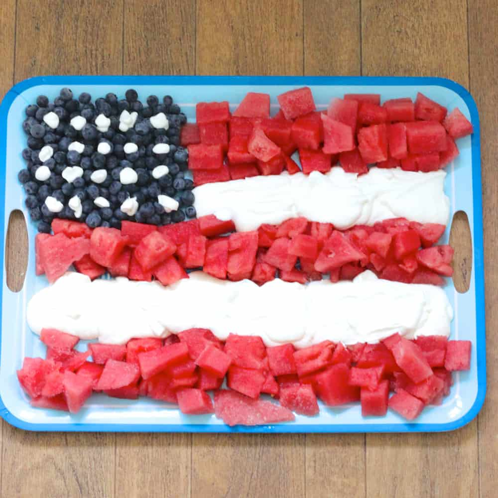 blueberries, watermelon and whipped cream in an American flag shape on a blue platter on wooden background