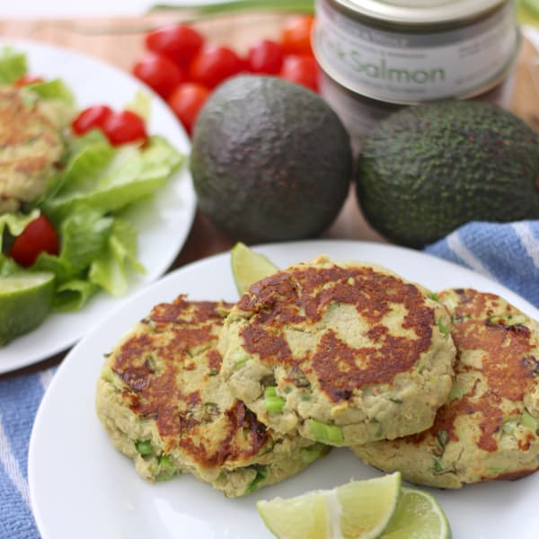 Avocado Salmon Burgers on a plate with lime slices, avocados, and canned salmon
