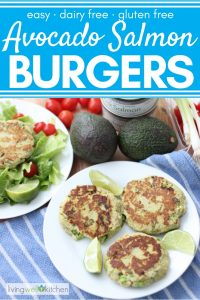 three salmon burgers on white plate with lemon slices, avocado, tomatoes, salmon cans