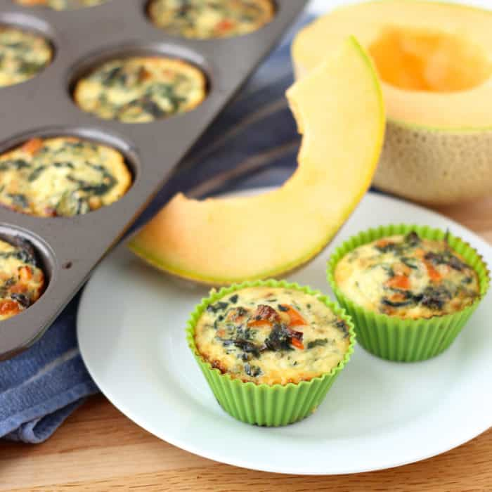 egg muffins on white plate with cantaloupe slice and muffin tin