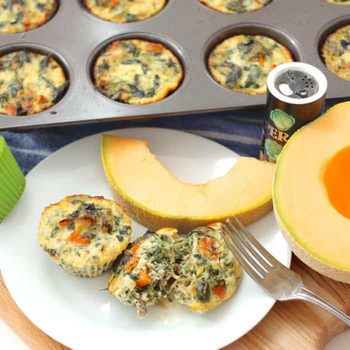 cut open Egg Muffins served with cantaloupe, extra egg muffins in muffin tin, pepper
