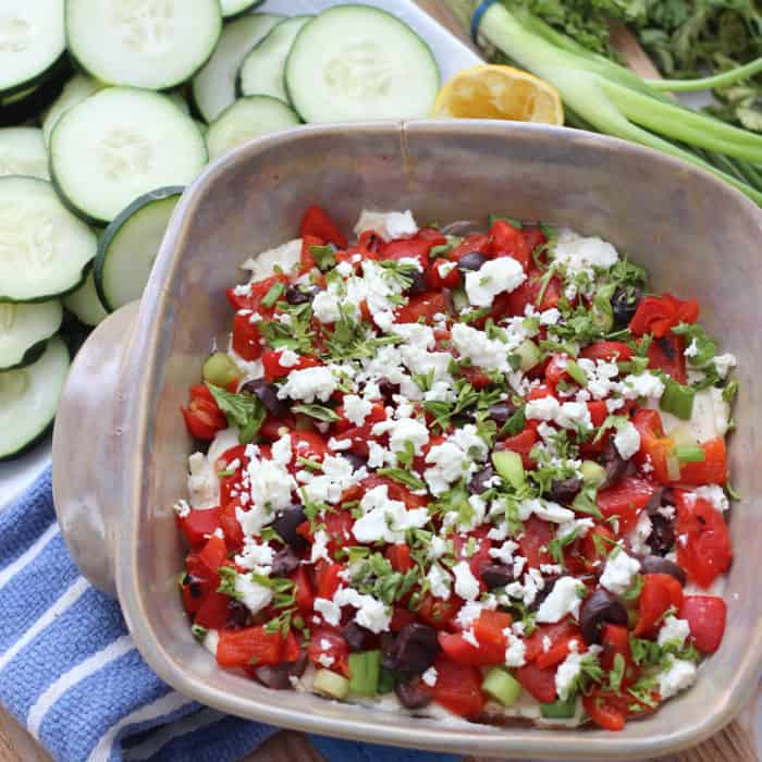 casserole dish with greek dip of cream cheese, roasted red bell peppers, olives, feta, and cucumbers