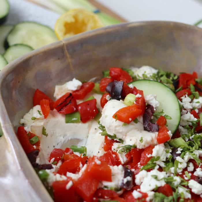 cucumber slice scooping cream cheese, roasted red peppers, olives, and feta dip out of casserole dish