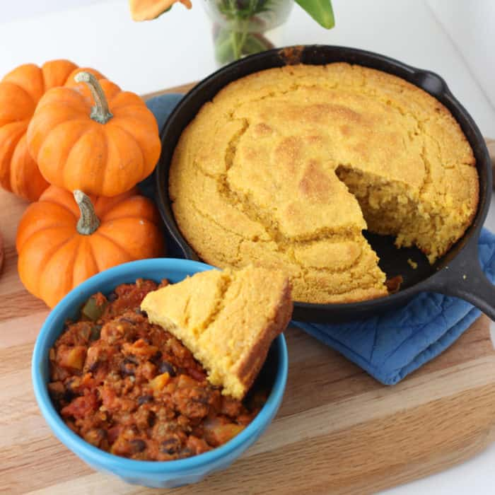 blue bowl of Pumpkin Chili with Pumpkin Cornbread in a cast iron skillet on wooden cutting board with three small pumpkins