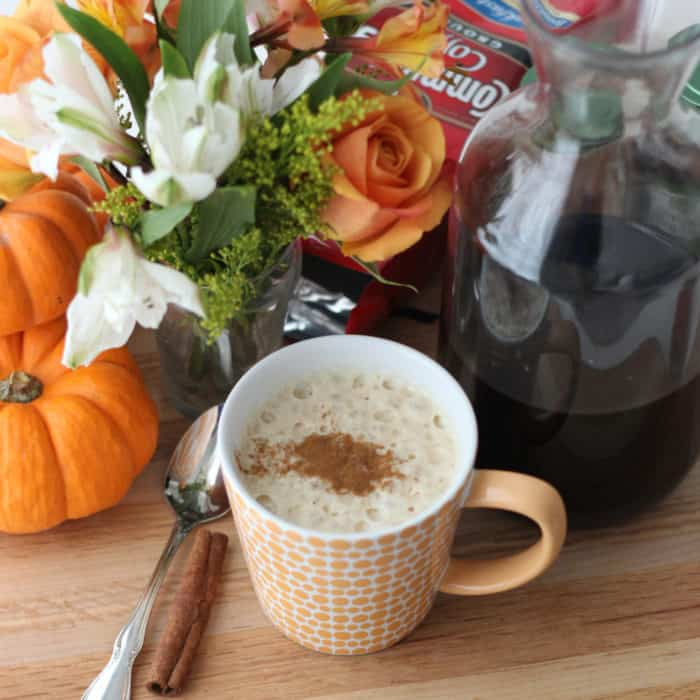 pumpkin spiced latte in orange and white mug, cold brew pumpkin coffee, flowers, pumpkins