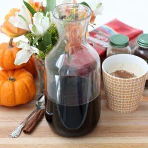 canister of Pumpkin Coffee Concentrate with homemade pumpkin spice latte, pumpkins, flowers, cinnamon sticks, coffee