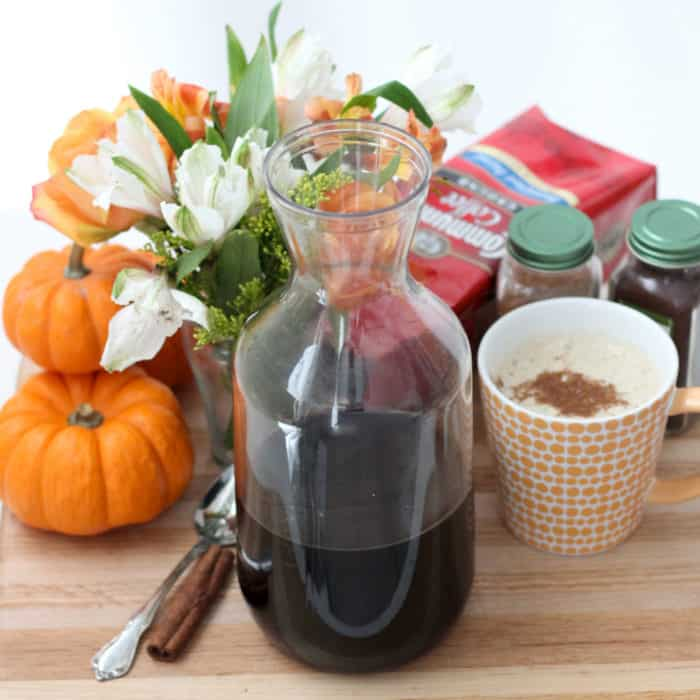 canister of Pumpkin Coffee Concentrate with homemade pumpkin spice latte, pumpkins, flowers