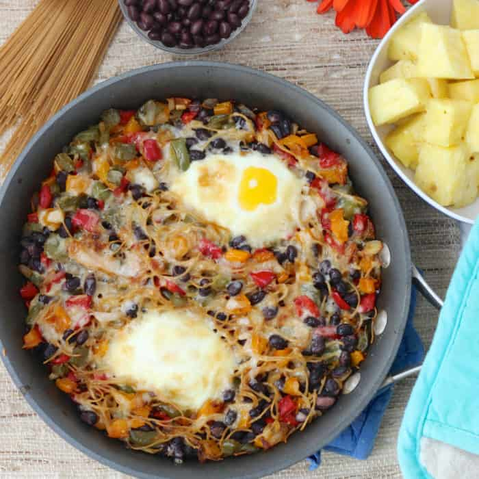Breakfast Pasta in a dark grey skillet with dry pasta, black beans, pineapple, blue hot pads