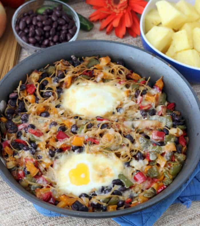 grey skillet with breakfast pasta and eggs, black beans and pineapple