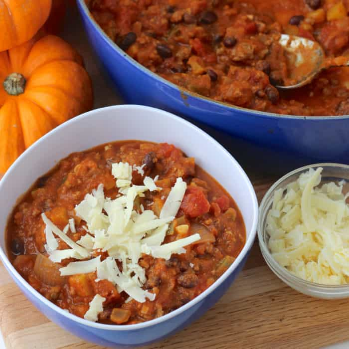 blue bowl of Pumpkin Chili with blue pot of chili and small bowl of cheese with small pumpkin