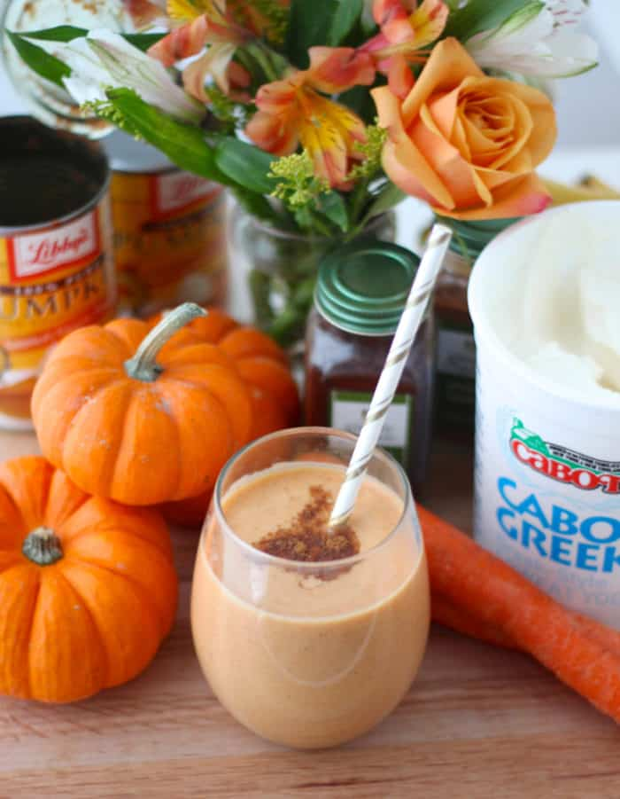 pumpkin pie smoothie with white and gold straw in glass, mini pumpkins, carrots, greek yogurt, flowers, spices