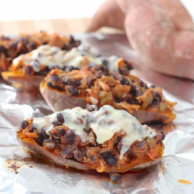 stuffed sweet potatoes topped with cheese on foil with sweet potatoes in the background