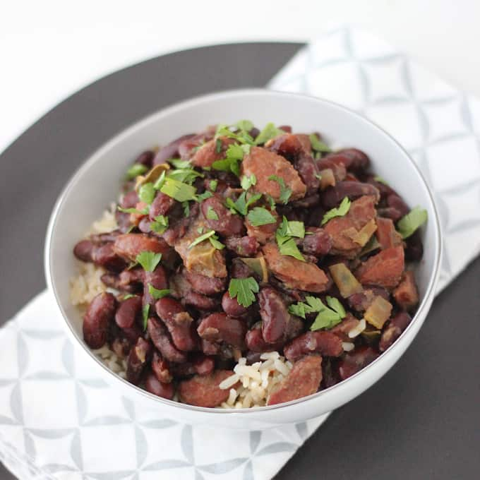 Red Beans and Rice sprinkled with parsley on a gray plate with silver and white napkin