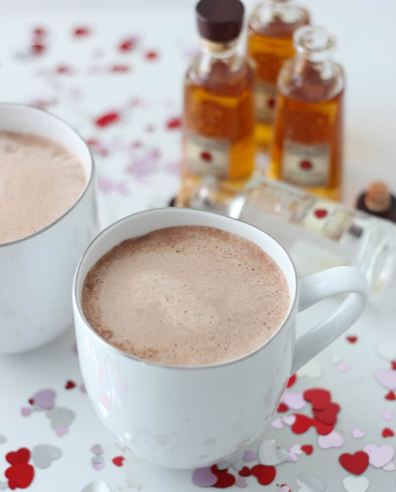 hot chocolate in two white mugs with bourbon in background and heart confetti on table