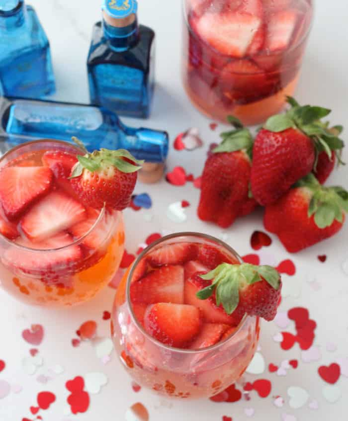 strawberry gin fizz in two clear wine glasses on table covered with heart confetti