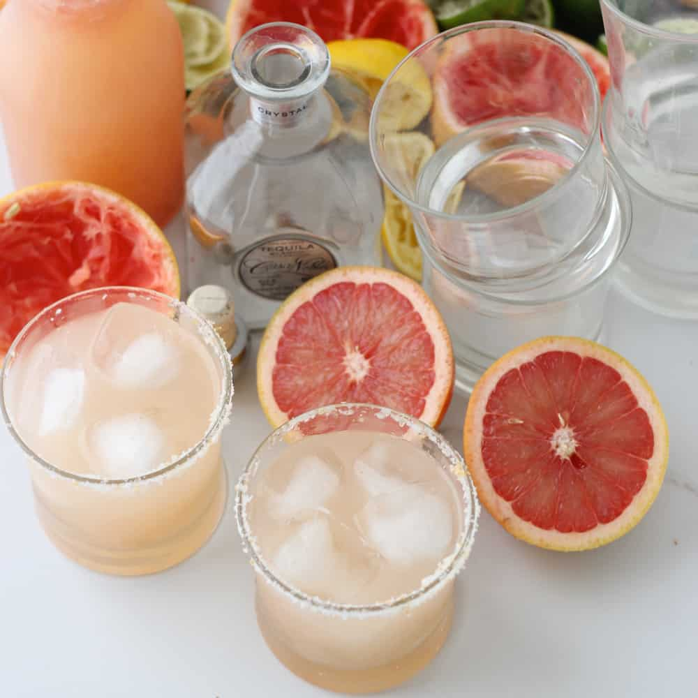 two glasses of Grapefruit Margaritas with fresh grapefruits and tequila