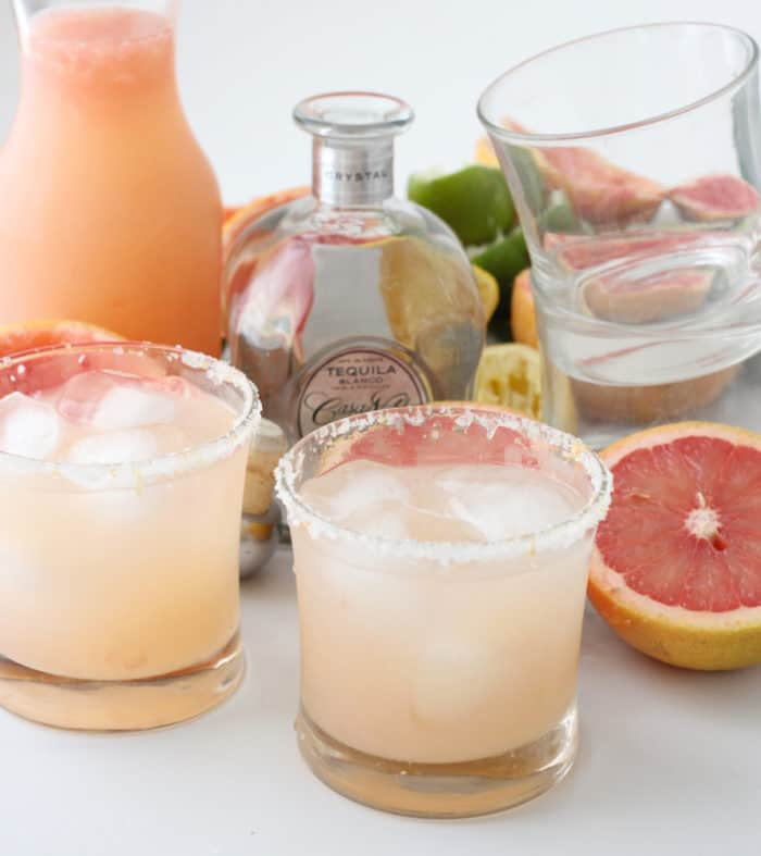 pitcher and two glasses of Grapefruit Margaritas, tequila bottle, grapefruit, empty glasses