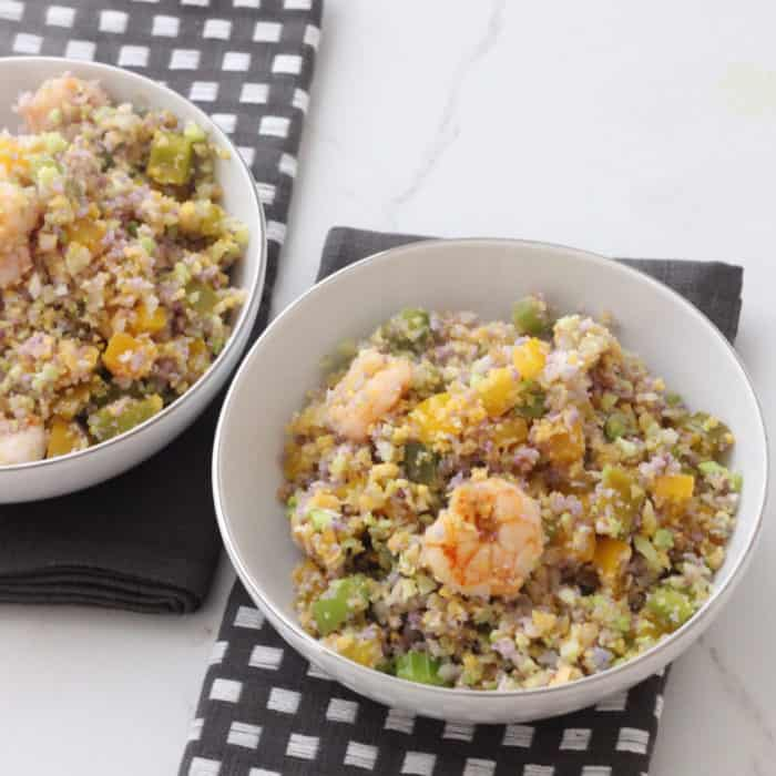 two bowls of Mardi Gras Fried Cauliflower Rice on top of white counter with slate colored napkins