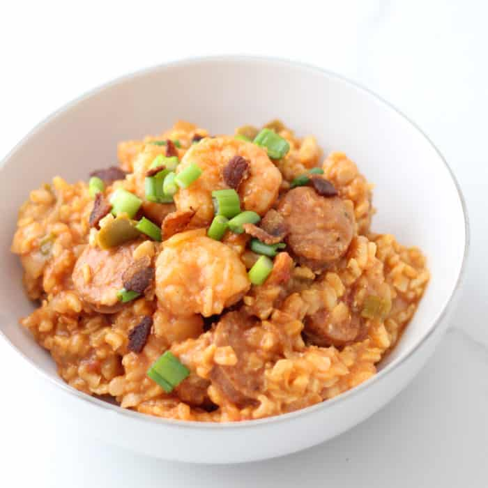 white bowl of shrimp and sausage Jambalaya with bacon and green onions
