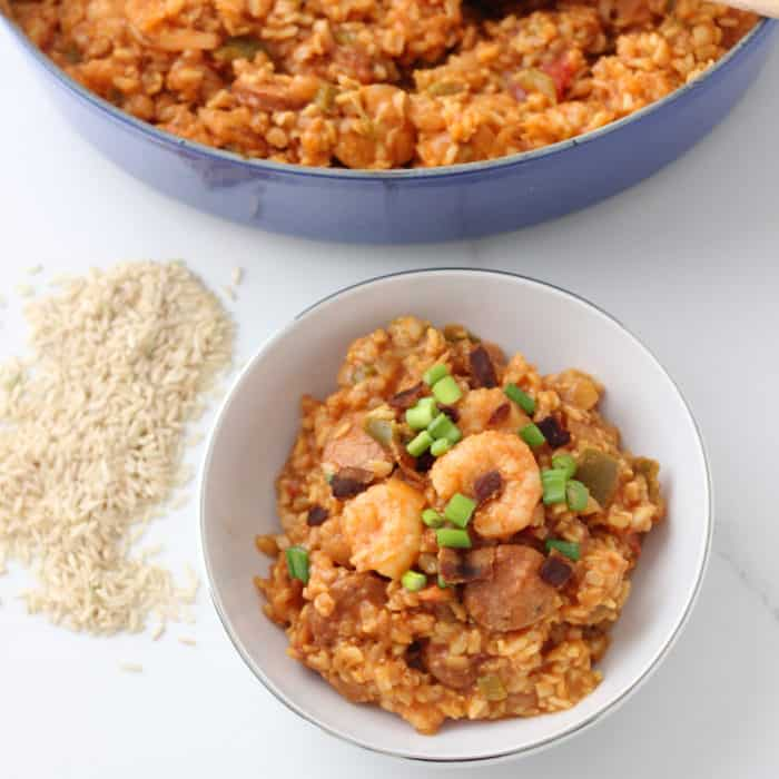 white bowl of shrimp and sausage Jambalaya with uncooked rice and blue pot of jambalaya