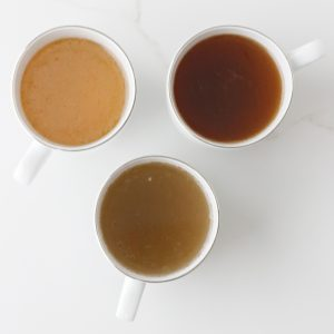three white cups with different types of bone broth