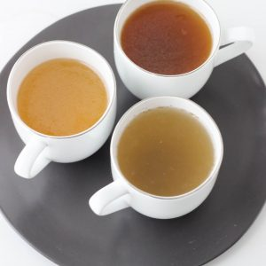 three cups of bone broth on grey plate