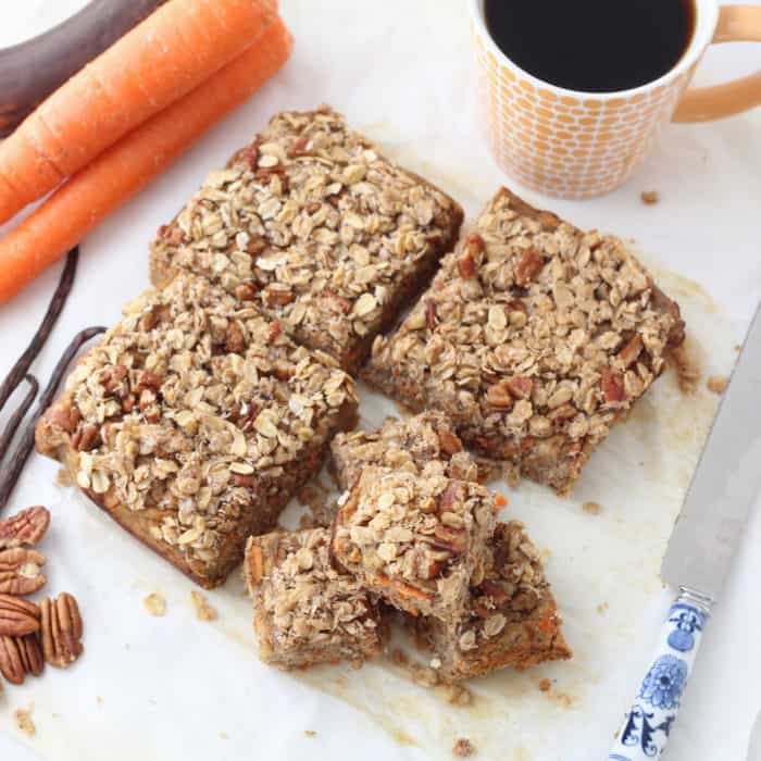 Coconut Carrot Coffee Cake with crumb topping cut into squares on parchment paper with knife, carrots, ripe banana, pecans, tea