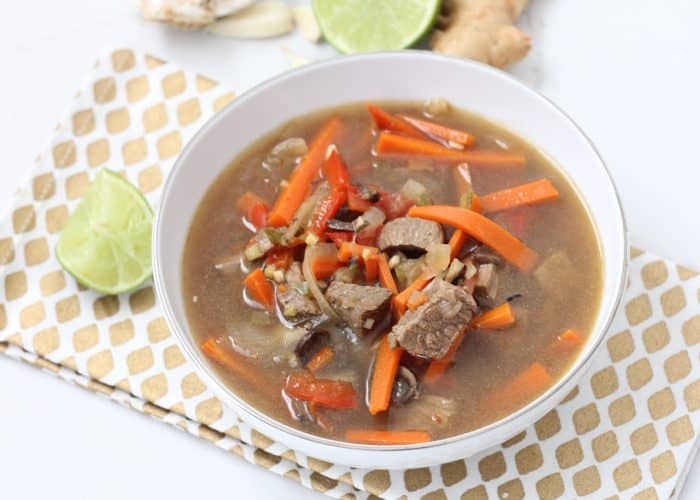 bowl of ginger beef soup with limes