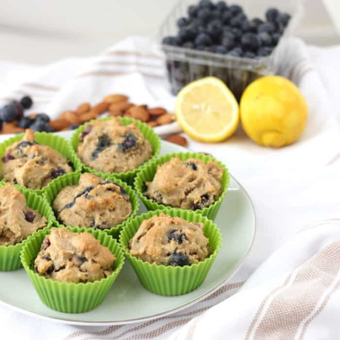 plate of Blueberry Almond Muffins in green silicone liners, cut lemons, fresh blueberries, whole almonds