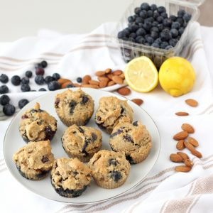 Blueberry Almond Muffins on white plate on white and tan dish towel with fresh blueberries, whole almonds and cut lemon