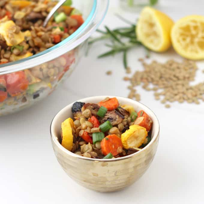 small cup of Roasted Vegetable Lentil Salad with big bowl of salad, lentils, lemons, and rosemary