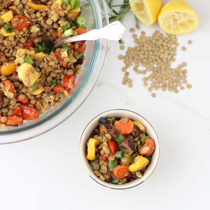 cup of Roasted Vegetable Lentil Salad with bowl of salad, lentils, lemon, and rosemary