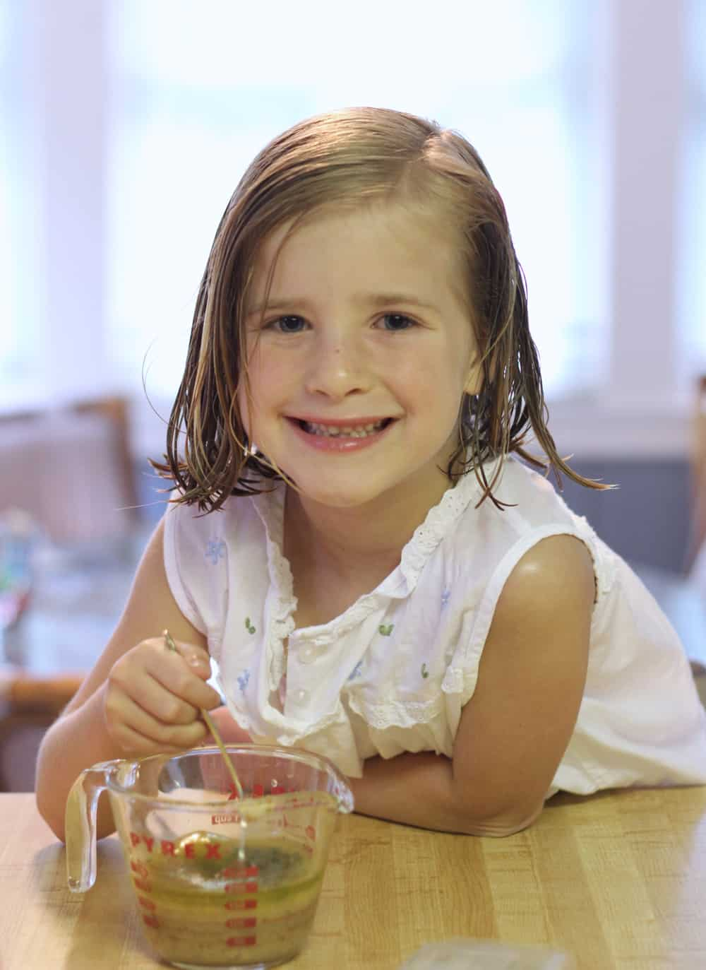 smiling little girl in white nightgown stirring a marinade in a glass measuring cup