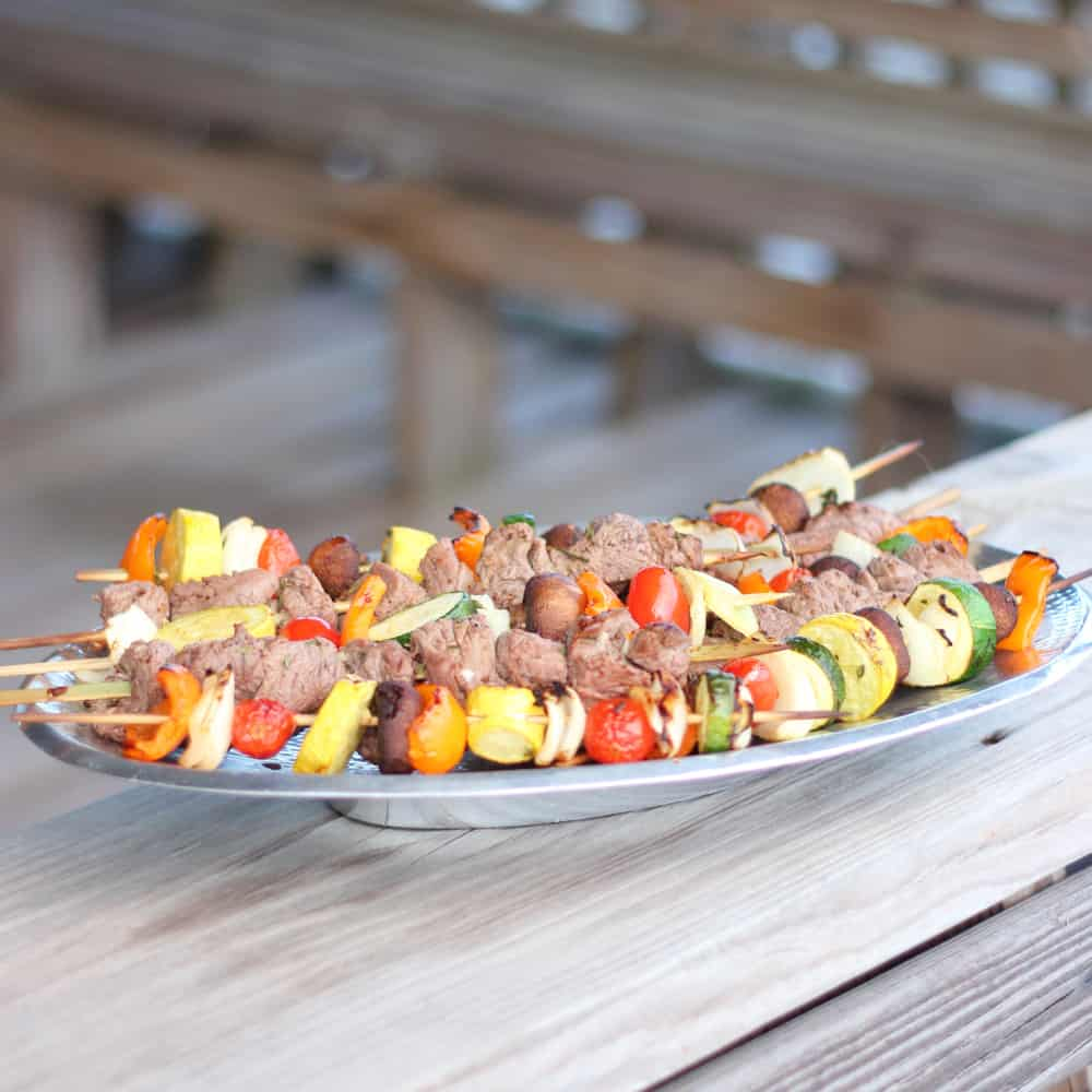 silver platter on wooden pier with lamb and vegetable kabobs