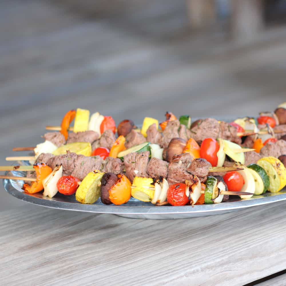 silver platter with lamb and vegetable kabobs