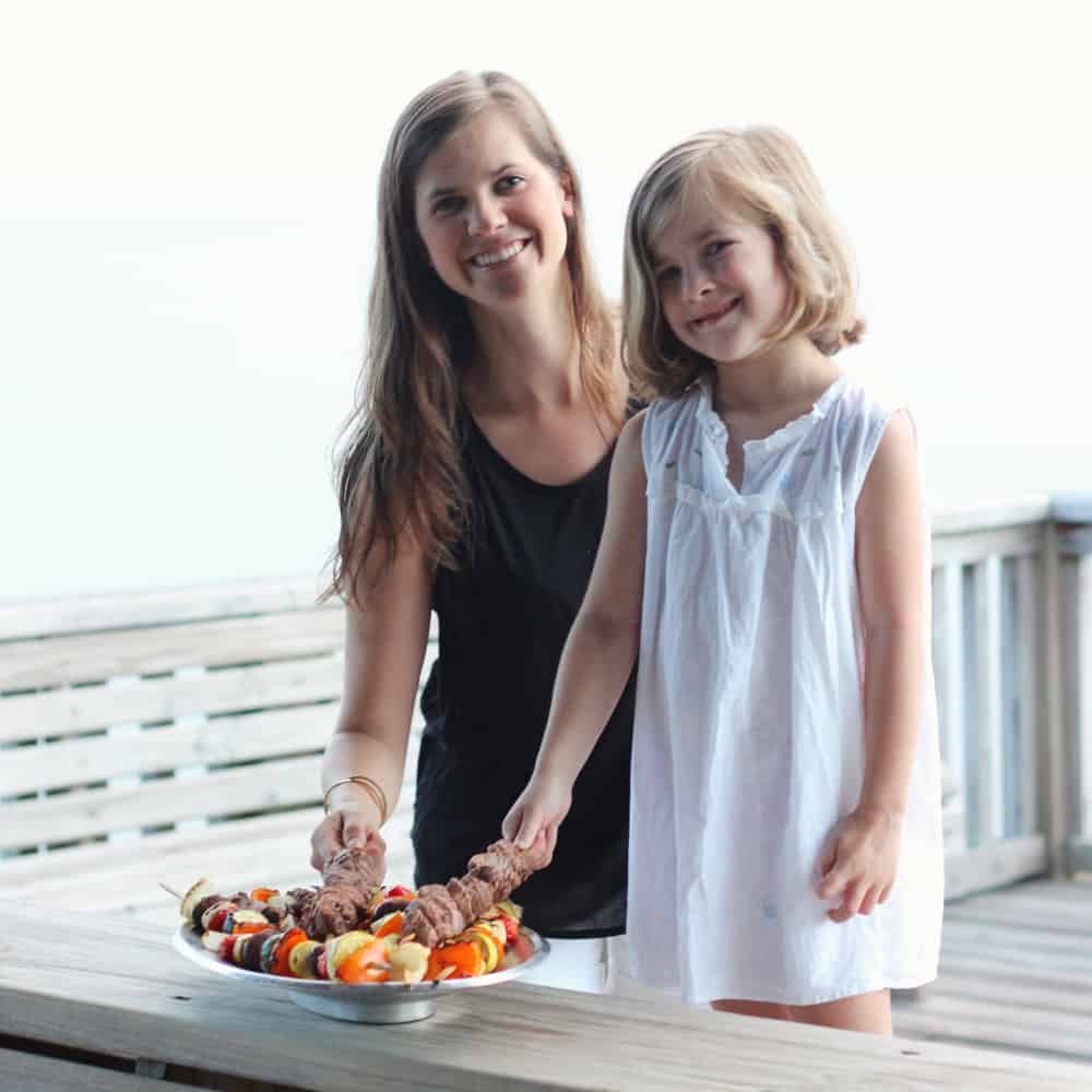 aunt and girl smiling while holding lamb kabobs on a wooden pier