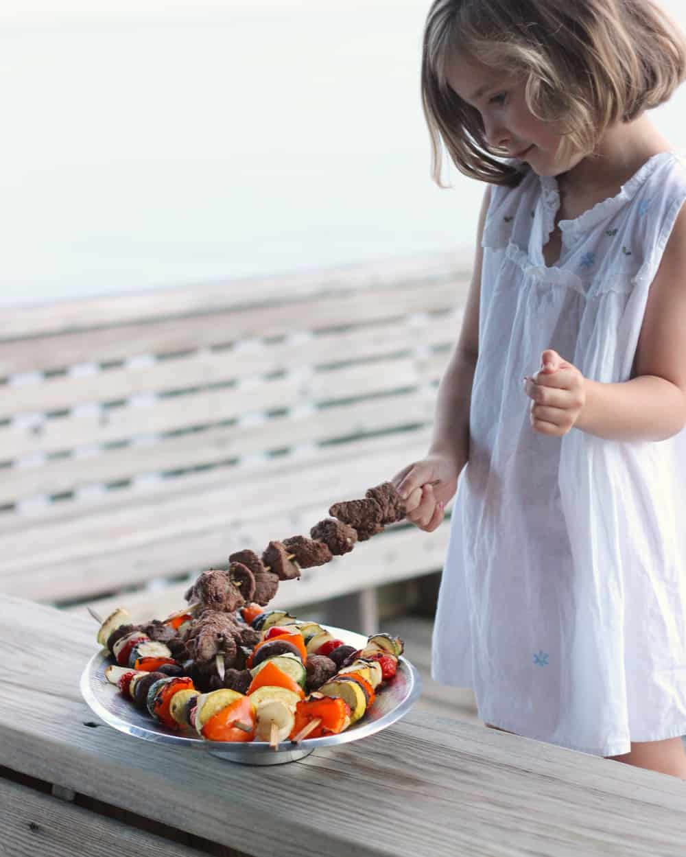 little girl taking a lamb kabob off a silver platter with lamb and vegetable kabobs