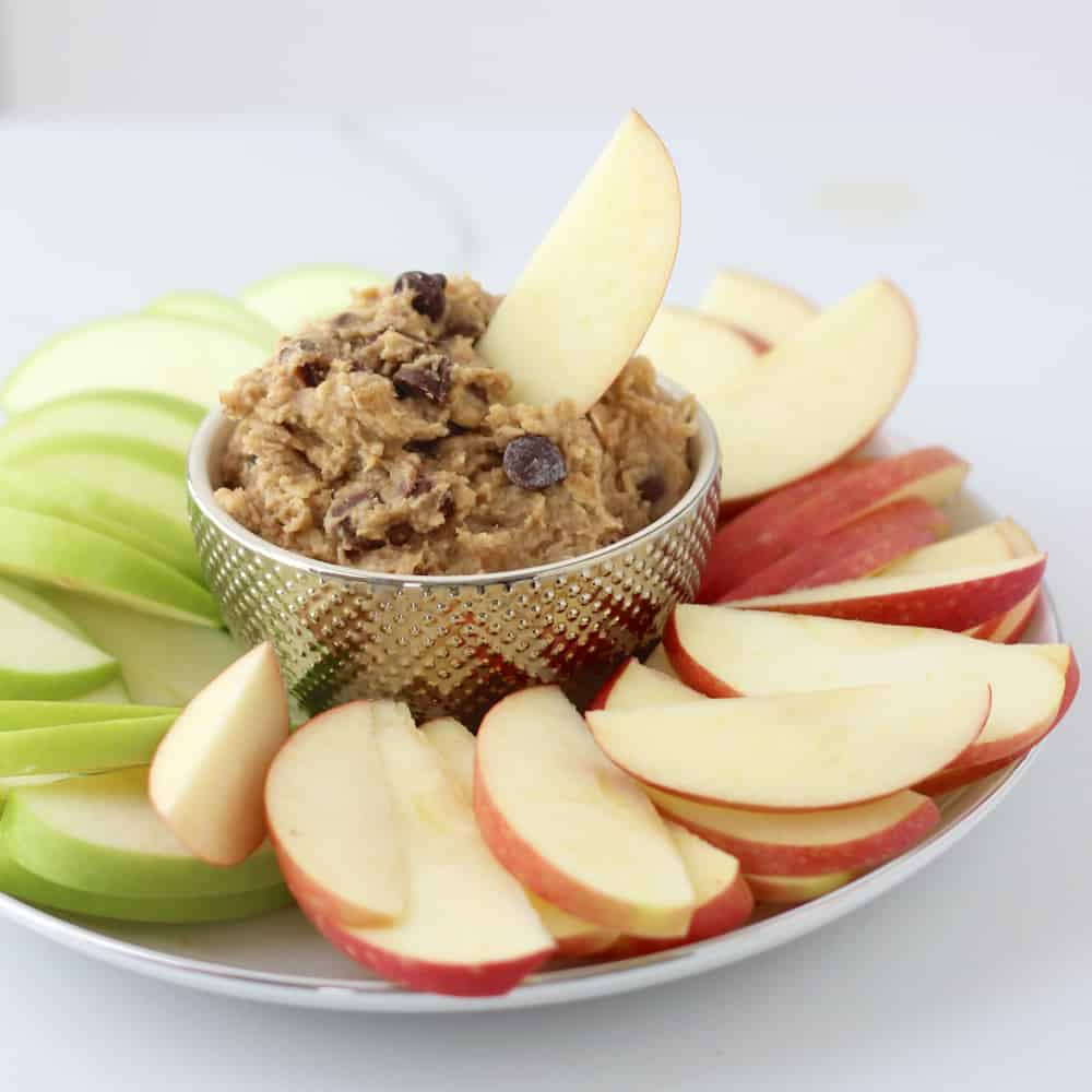 plate of sliced red and green apples with a bowl of Chocolate Chip Cookie Dough Dip