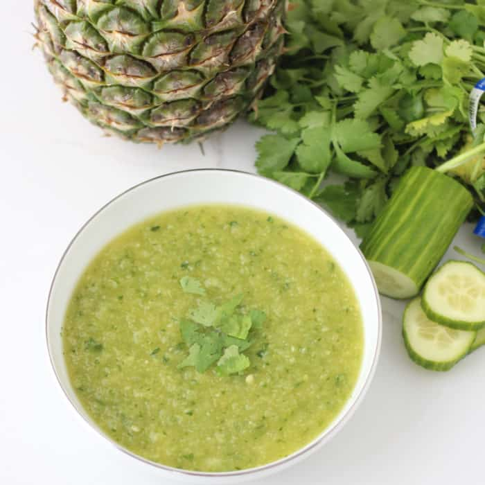 pineapple cucumber gazpacho in a white bowl with whole pineapple, cilantro, sliced cucumber
