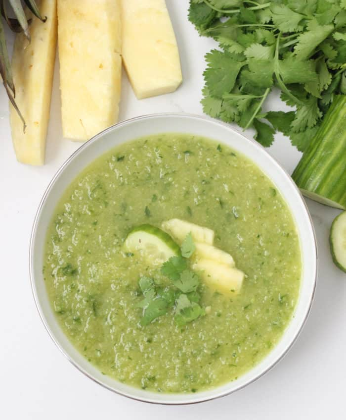 fresh pineapple, cilantro, cucumbers next to a bowl of pineapple gazpacho