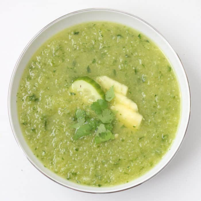 white bowl of Pineapple Cucumber Gazpacho topped with fresh pineapple, cilantro and cucumber