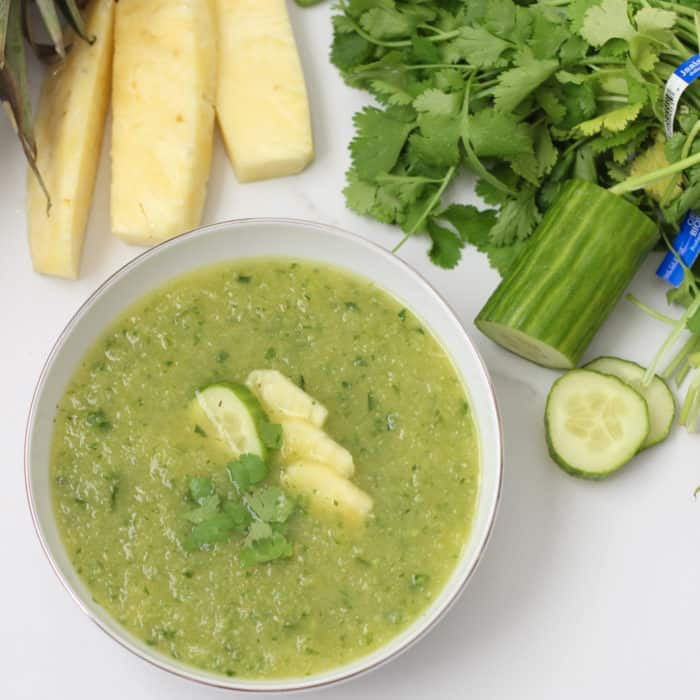 Pineapple Cucumber Gazpacho in a white bowl with fresh pineapple, cilantro and cucumber