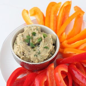 plate of sliced orange and red bell peppers, bowl of eggplant hummus