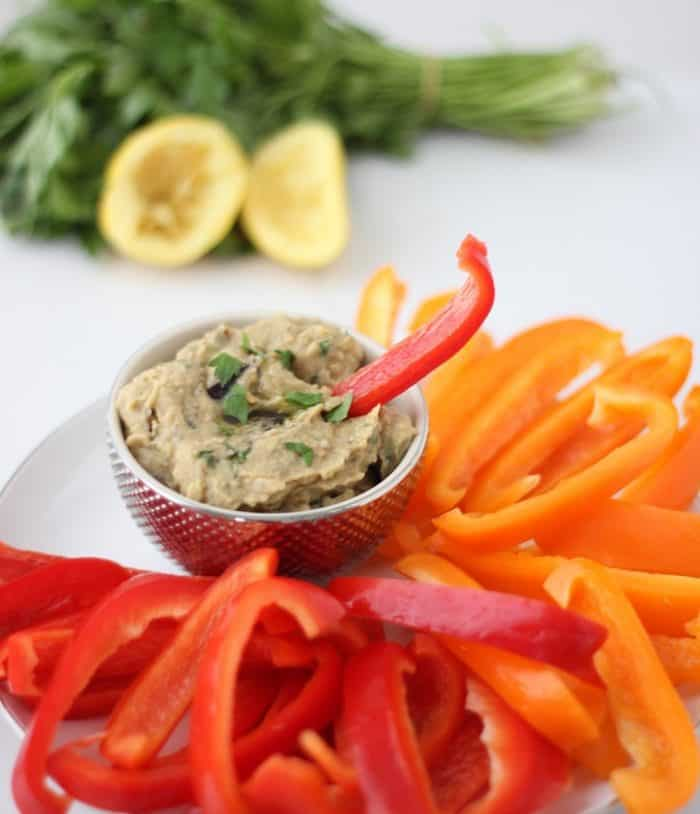 roasted eggplant hummus in a small gold bowl with a red bell pepper sticking out of hummus, lemon, parsley, bell peppers