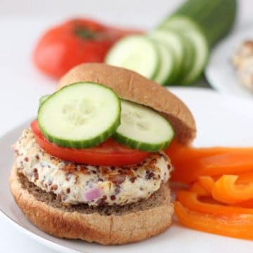 Greek Turkey Quinoa Burgers on a bun with cucumbers and tomato