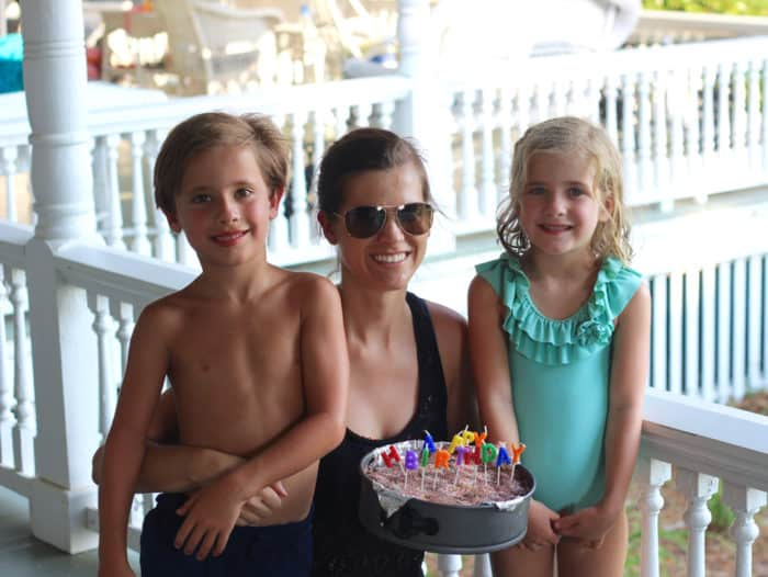 boy and girl with their aunt holding a happy birthday ice cream cake